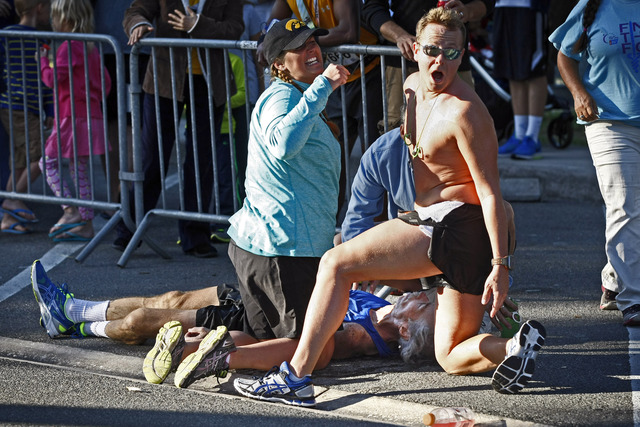 David James, 32, of Fort Myers and another yell for medial help as fallen Greg Wolpert, 59, of Naples suffers from cardiac arrest during the Naples Daily News Half Marathon Sunday, Jan. 18, 2015 in downtown Naples, Fla. Just under 2,400 people registered to race. Kenyans Cleophas Ngetich and Zipporah Chebeat were the male and female winners of the 2015 Naples Daily News Half Marathon on Sunday. First responders resuscitated Wolpert on scene saving his life.(Corey Perrine/Staff)